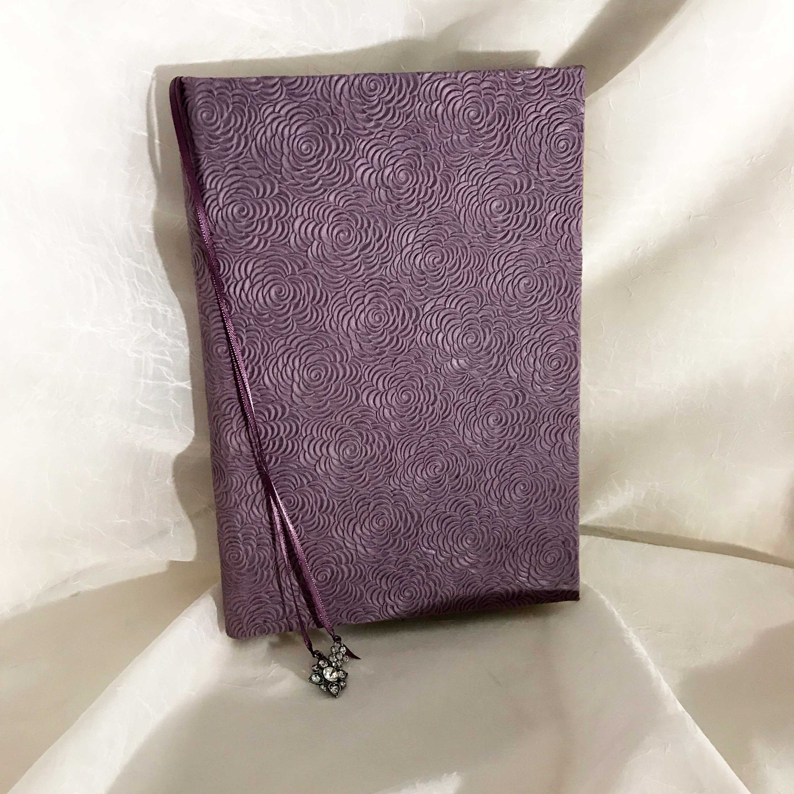 Perfect bound notebook with embossed lilac paper. $45